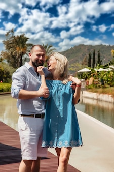 Loving couple enjoying honeymoon in luxury hotel, walking through grounds with palm trees and swimming pool. happy lovers on romantic trip have fun on summer vacation. concept romance and relaxation