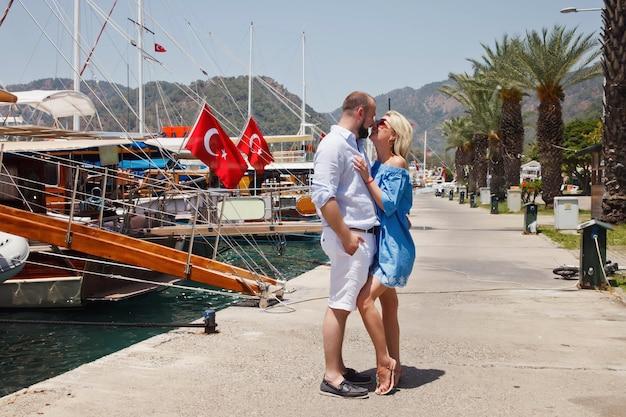 Влюбленная пара наслаждается медовым месяцем на набережной с роскошными яхтами