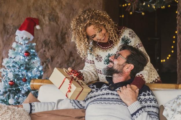 愛するカップルはクリスマスに自宅で贈り物を交換します