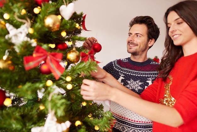 Coppie amorose che appendono le decorazioni sull'albero di natale