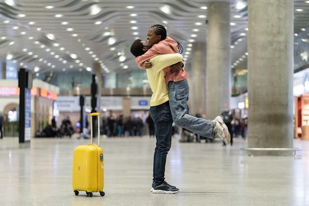 長い間アフリカの男性と女性が空港ターミナルで抱擁を興奮させた後の愛情のあるカップルの幸せな会議