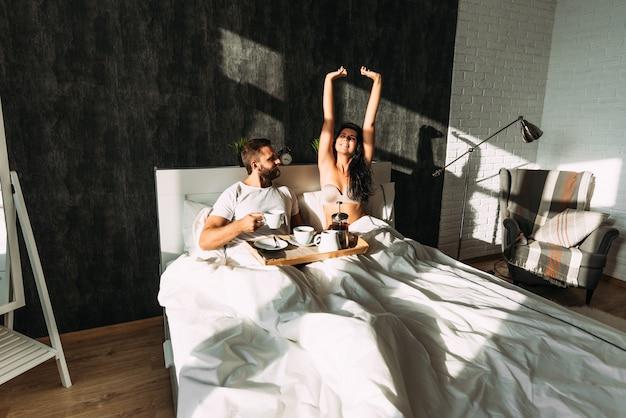 침대에서 아침을 먹고 사랑하는 부부