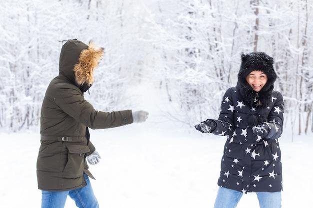 雪の公園で屋外で楽しんでいる愛情のあるカップル