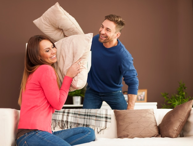 Loving couple having a pillow fight at home