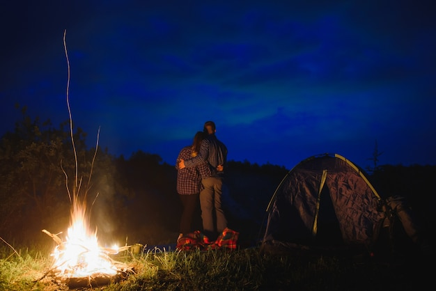 Loving couple hikers enjoying each other, standing by campfire at night under evening sky near trees and tent