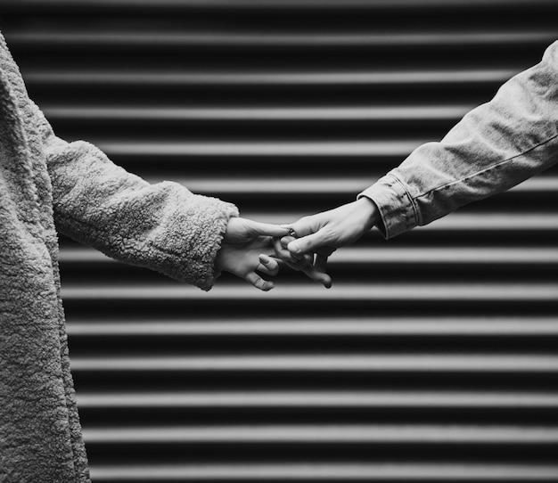 Влюбленная пара держится за руку. черно-белое фото.