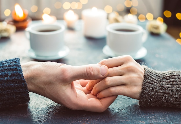A loving couple hold hands at a romantic dinner in restaurant with candles.