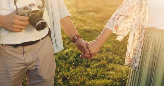 Влюбленная пара, взявшись за руки крупным планом. женщина и мужчина, держащий руку