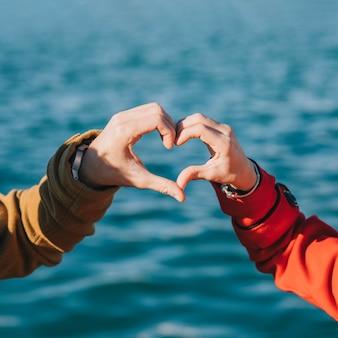 Loving couple holding hands in heart shape