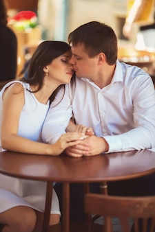 Loving couple holding hands, sitting in cafe