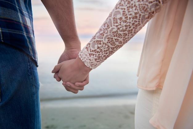 Влюбленная пара, взявшись за руки вместе