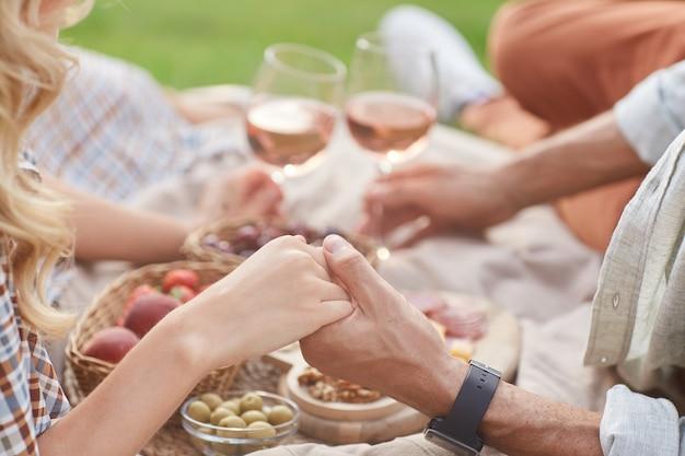 ロマンチックなデート中に屋外でピクニックを楽しみながら手をつないで愛するカップル