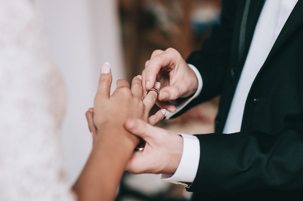Loving couple holding hands with rings against wedding dress
