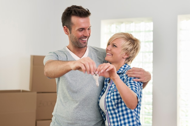 Влюбленная пара держит ключ от нового дома