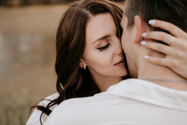 Влюбленные обнимаются на закате летом. брюнетка девушка в легком платье. история о любви.