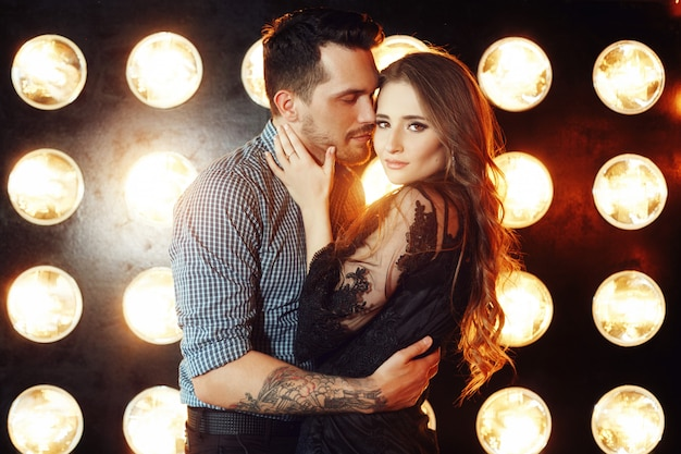 Loving couple hugging on the couch against the bright lights of lamps. passion and tenderness, man and woman love each other. girl hugging a man