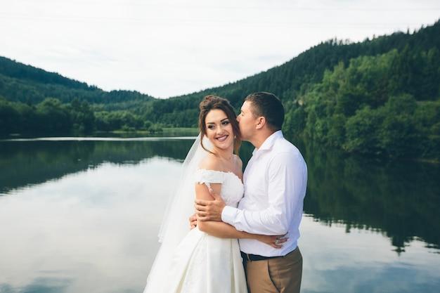 山の湖の背景に抱き締める愛情のあるカップル
