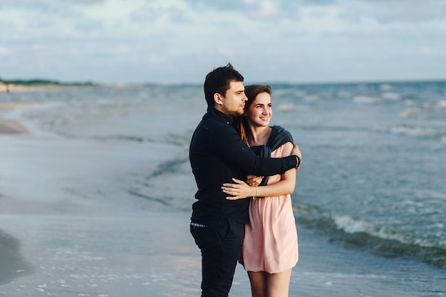 Loving couple hugging at sunset at sea