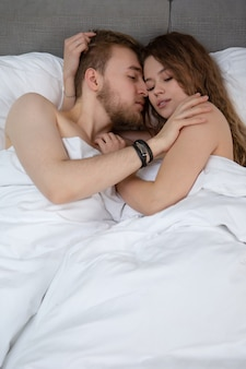 Loving couple hugging while lying in bed