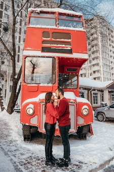 A loving couple hugs on the background of a red bus. valentine's day. high quality photo