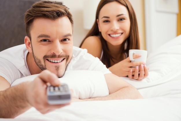 침대에서 사랑하는 부부. 아름 다운 젊은 부부는 함께 침대에 누워 원격 제어를 들고 남자 동안 웃 고