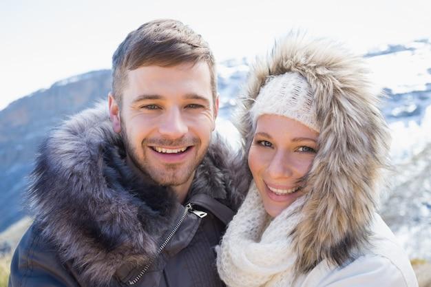 Любящая пара в куртках против снежной горы