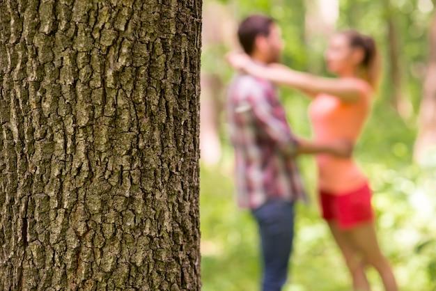공원에서 사랑하는 부부. 나무 줄기와 배경에서 포옹하는 사랑하는 부부의 클로즈업 이미지
