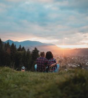格子縞のシャツを着た愛情のあるカップルが山の頂上で夕日に出会います。