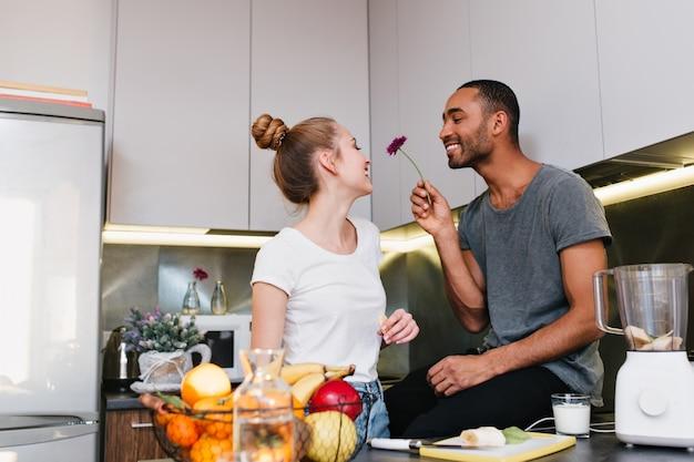 キッチンでいちゃつくtシャツの愛情のあるカップル。夫は彼の妻に美しい花を与えます。幸せそうな顔、素敵な贈り物、健康的な食事、幸せなペア。