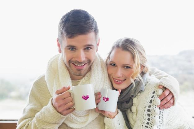 Любящая пара в зимней одежде с кофейными чашками против окна