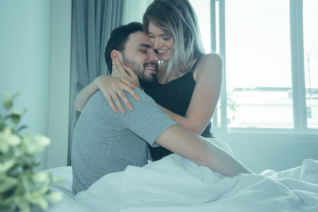 Loving couple kissing in bed.happy couple lying together in bed.