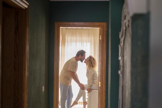 愛するカップルが家でお互いにキスします。集合住宅でキスする愛情のこもったカップルのプロフィール。家の国内の部屋の中でキスするロマンチックな男と女