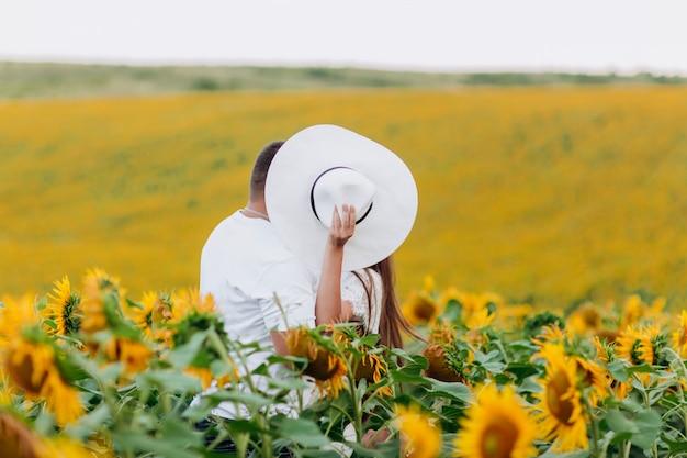 ひまわり畑でキスする愛情のあるカップル。自然に一緒に時間を過ごす家族。セレクティブフォーカス