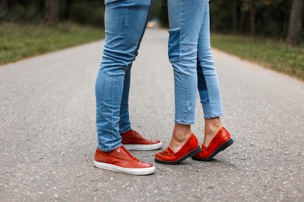 Влюбленная пара, целующаяся в дороге. мужские и женские ножки в стильной обуви на асфальте