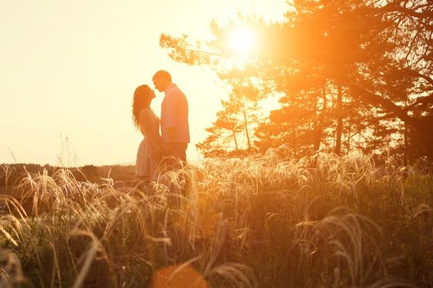 Loving couple kissing at sunset