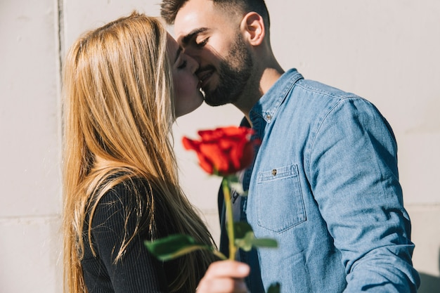 Loving couple kissing with rose in hand