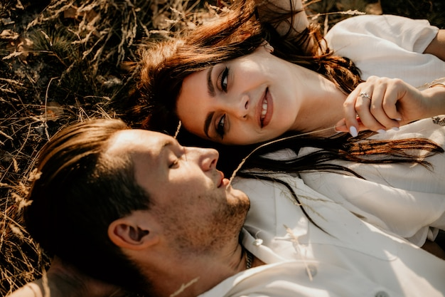 Влюбленная пара, лежа на траве на закате в летнее время. брюнетка девушка в легком платье. история о любви.