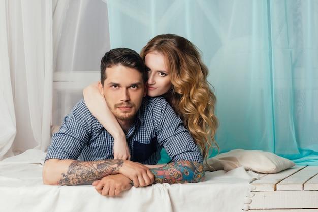 Loving couple lies near window tender and romantic