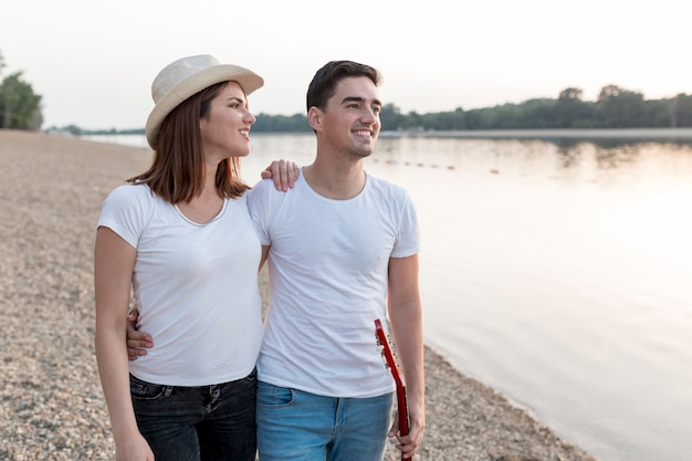 Loving couple looking away by the lake