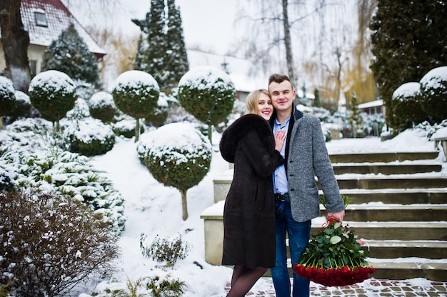 Loving couple in love at winter day with large bouquet