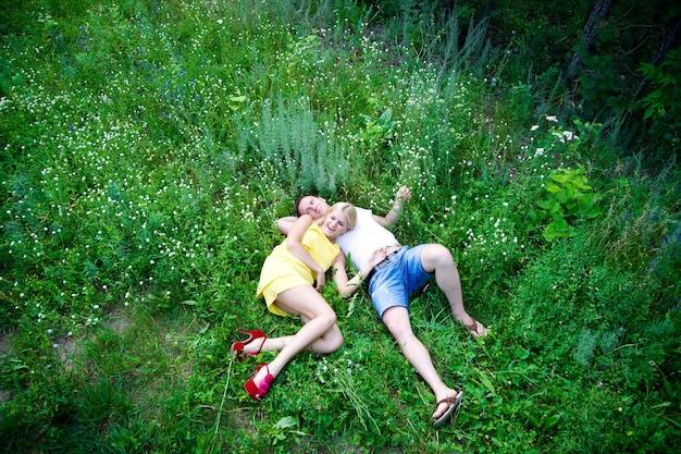 夏に緑の草の上に横たわる愛情のあるカップル