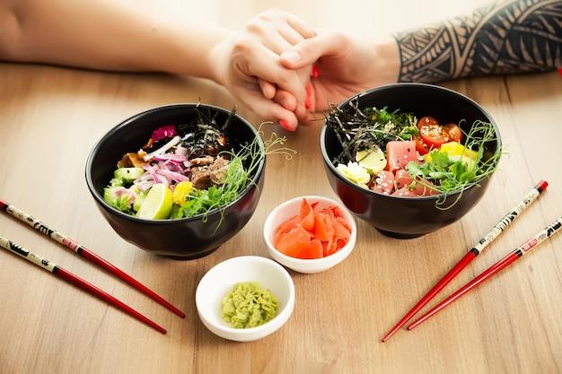 샐러드를 먹는 사랑하는 커플 남녀가 젓가락을 찔러 참치 샐러드를 그릇에 넣습니다.
