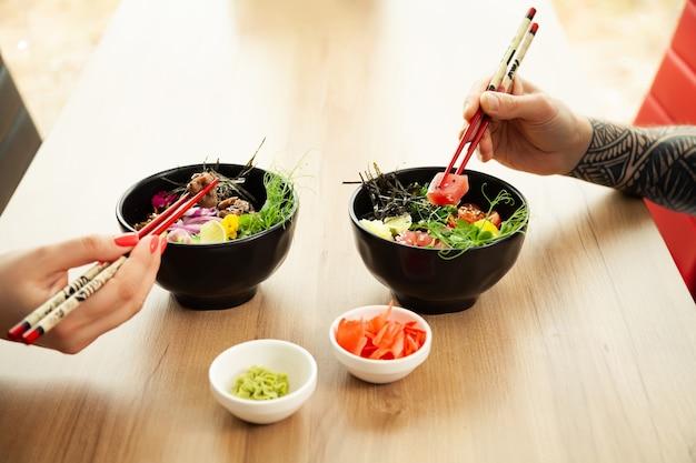 사랑 하는 커플 남자와 여자 샐러드를 먹고 젓가락 찌르다. 참치 샐러드를 그릇에 담습니다. 식당에 있는 사람들은 젓가락으로 샐러드를 먹습니다. 아시아 해산물 샐러드 개념입니다.