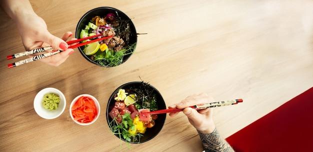 샐러드를 먹는 사랑하는 부부 남녀가 젓가락을 찔러 참치 샐러드를 그릇에 담다 사람들