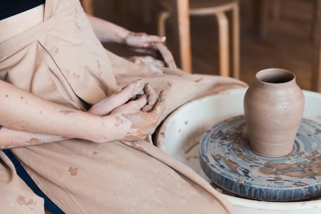 陶芸工房で愛するカップルの男性と女性がクローズアップ、ろくろに座って、花瓶を作り、陶器のワークショップでデート