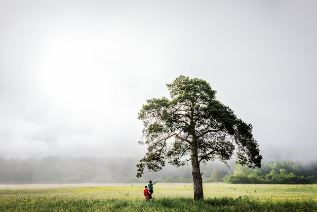Loving couple meets dawn in the field. misty morning. the guy and the girl near the tree. couple travels. man and woman in the field. lonely tree. the guy lifted up the girl. lovers travel. follow me