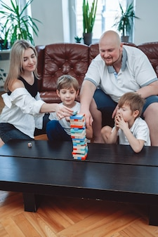 Loving couple of mother and father teach to play jenga game their little and cheerful boys sitting at table in modern apartment.