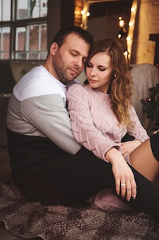 바닥에 크리스마스 트리 근처 사랑하는 부부