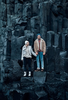 愛する観光客のカップルが黒い火山玄武岩の山の石に手をつないで立っています。