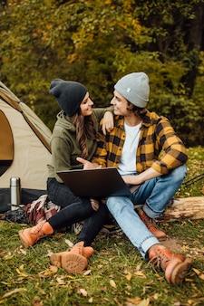 テントの近くの森で若いフリーランサーの愛情のあるカップルが映画を見る